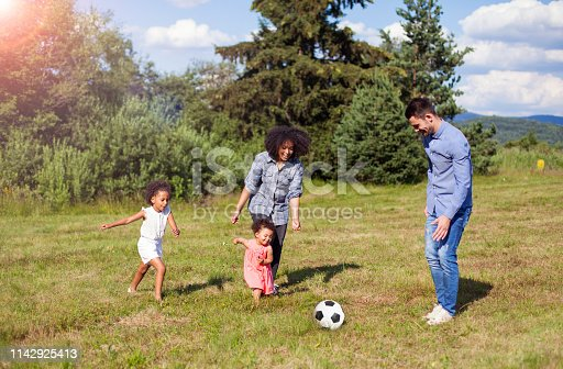 istock Family outdoors in summer playing soccer game in park 1142925413