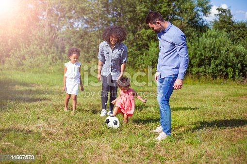 Family outdoors in summer playing soccer game in park