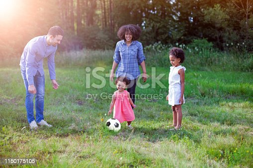 istock Family outdoors in summer playing soccer game in park 1150175105