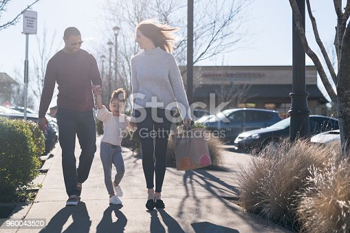 A pre-school age tugs her parents along outside the grocery store. They are outside on the sidewalk and she is holding their hands. Mom is carrying a paper bag of groceries. It's a sunny day.