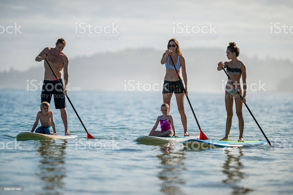 Family paddleboarding in Hawaii stock photo