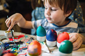 Cute family painting colourful Easter eggs