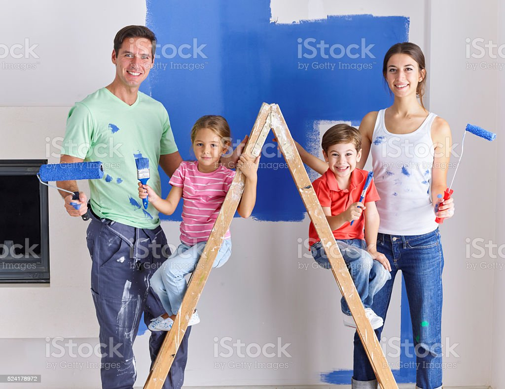 Family painting wall blue together stock photo