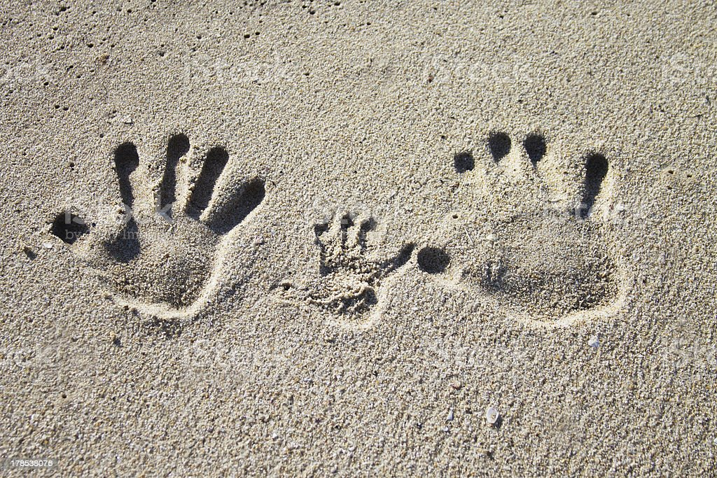 Family palm imprints on sand stock photo