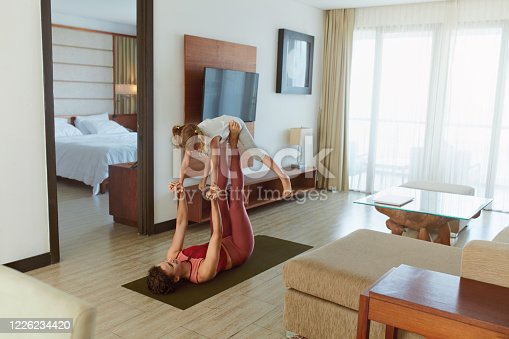 916126642 istock photo Family. Parent And Child Doing Partner Yoga At Home. Young Woman And Daughter Exercising Together. Sporty Kid And Mother Practicing Acroyoga In Living Room. 1226234420