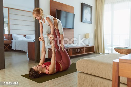 916126642 istock photo Family. Parent And Kid Doing Partner Yoga At Home. Sporty Child And Mother Practicing Acroyoga In Living Room. Young Woman And Daughter Exercising Together. 1226234493