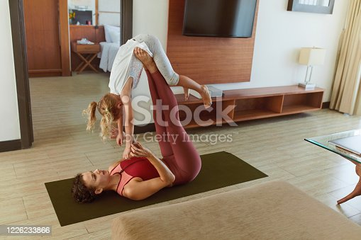 916126642 istock photo Family. Parent And Kid Exercising Together At Home. Young Woman And Child Doing Partner Yoga. Sporty Daughter And Mother Practicing Acroyoga In Living Room. 1226233866
