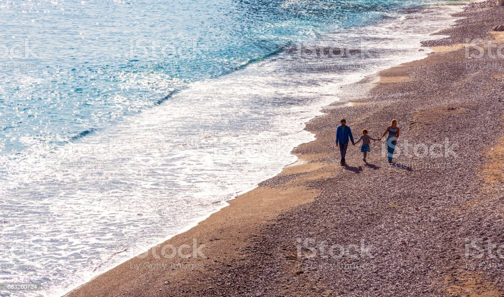 Family Parents and Child walking on rocky  Beach along Surf foto de stock royalty-free