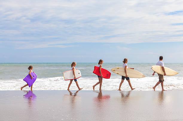 Family Parents Girl Children Surfboards on Beach stock photo