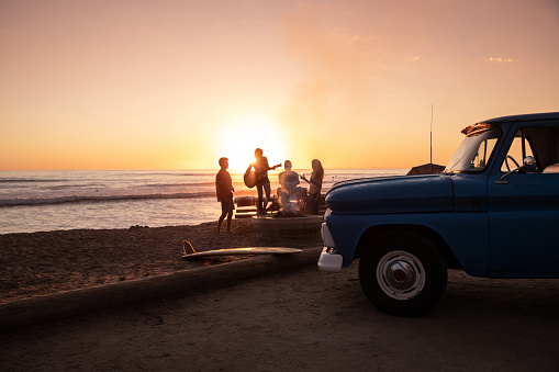 Family party on the beach in California at sunset