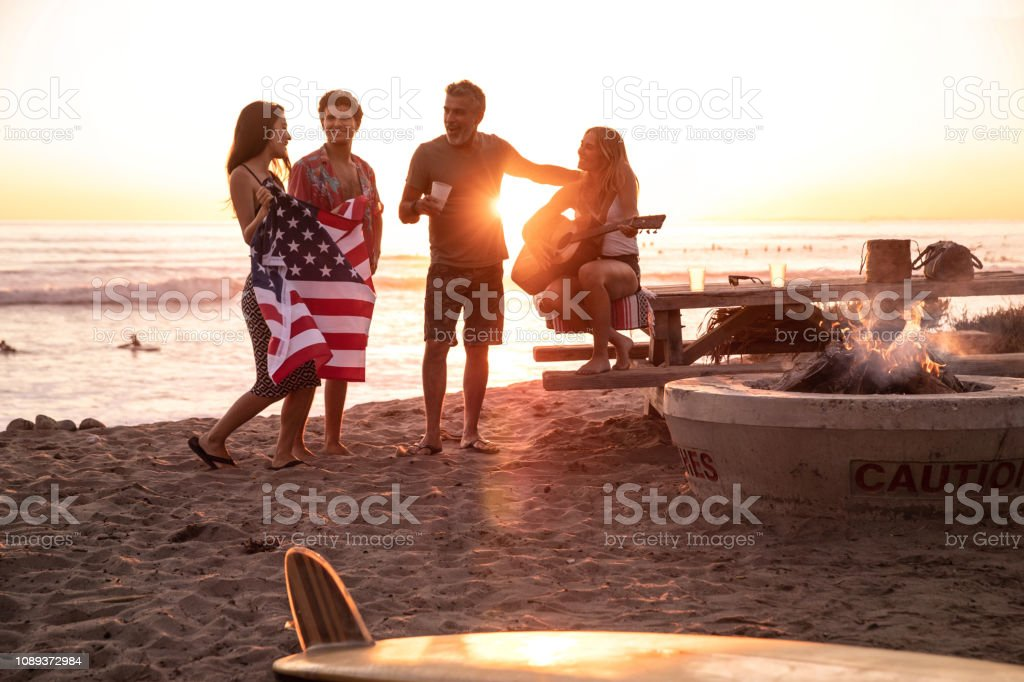 Family party on the beach in California at sunset stock photo