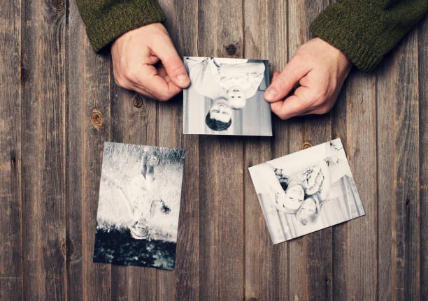 Familienfotos in Mannhände und auf verwitterten Holztisch. Ansicht von oben. – Foto