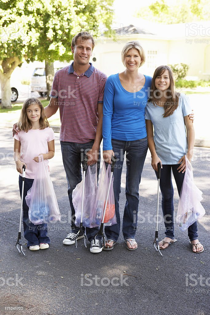 Family Picking Up Litter In Suburban Street royalty-free stock photo