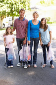 Family Picking Up Litter In Suburban Street Smiling To Camera.