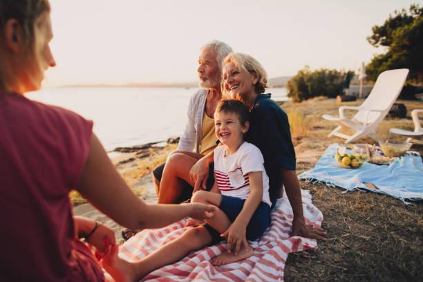 family picnic on the beach - pasto al sacco foto e immagini stock