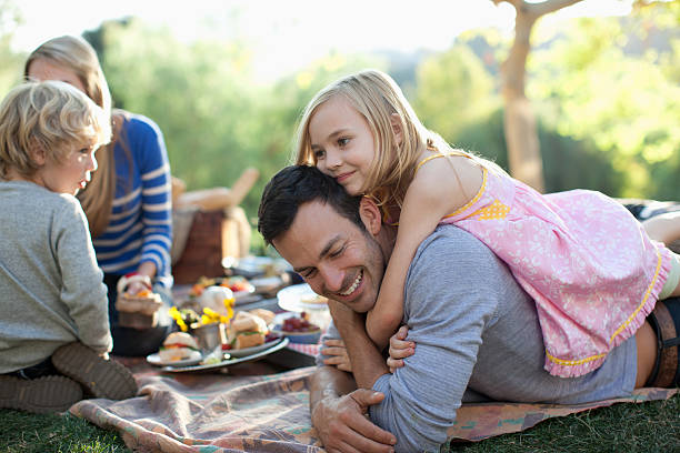 family picnicking together outdoors - picnic stock pictures, royalty-free photos & images