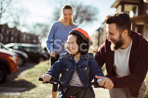 Close up of a happy young family outside riding a bike