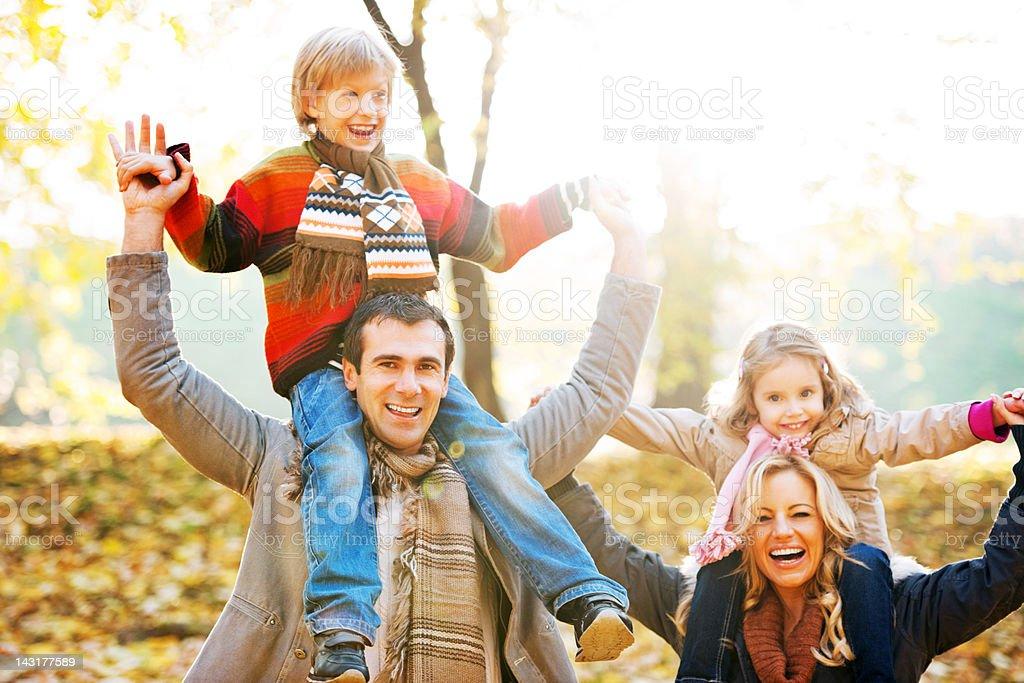 Family piggybacking their children in park. royalty-free stock photo