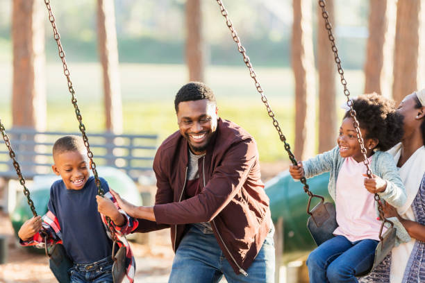 Family playing at park together, on swings stock photo