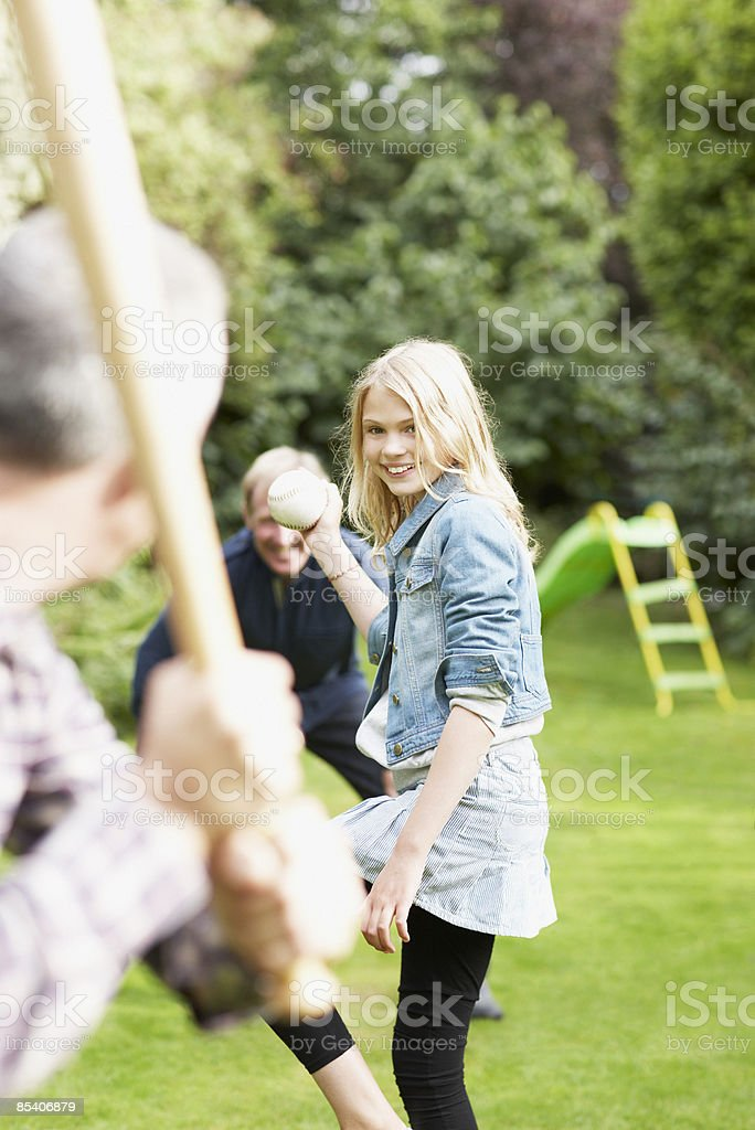 Family playing baseball in backyard royalty-free stock photo