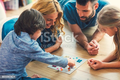 Family With Two Children Playing Board Game on The Floor At Home