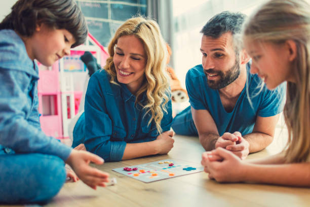 Family Playing Board Game At Home Family With Two Children Playing Board Game on The Floor At Home.*game table designed by vgajic leisure games stock pictures, royalty-free photos & images