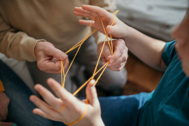 Family playing cats cradle stock photo