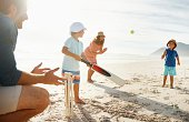 istock Family playing cricket at a beach in the sun 496877921