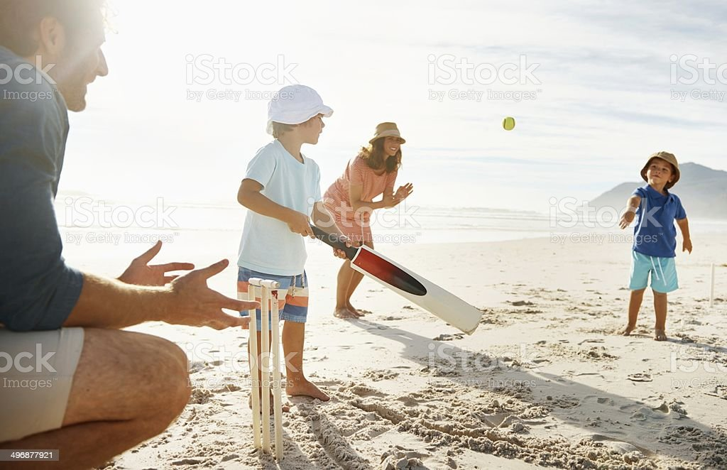 Family playing cricket at a beach in the sun stock photo