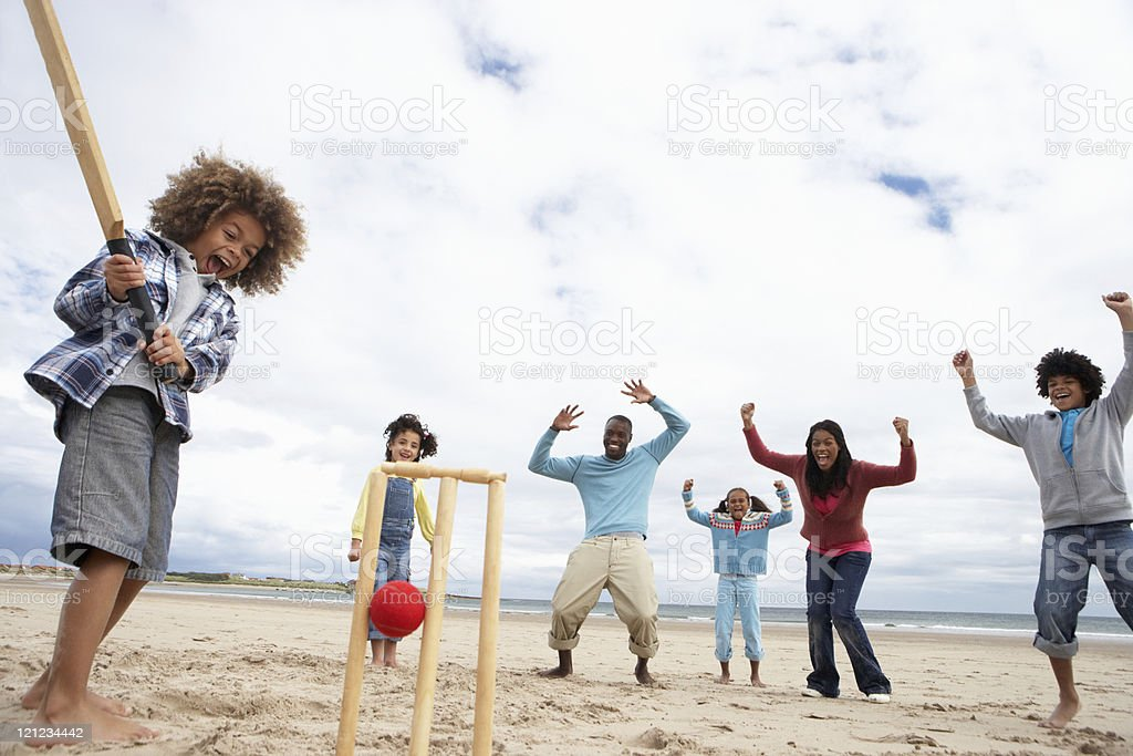 Family playing cricket on beach on a cloudy day stock photo