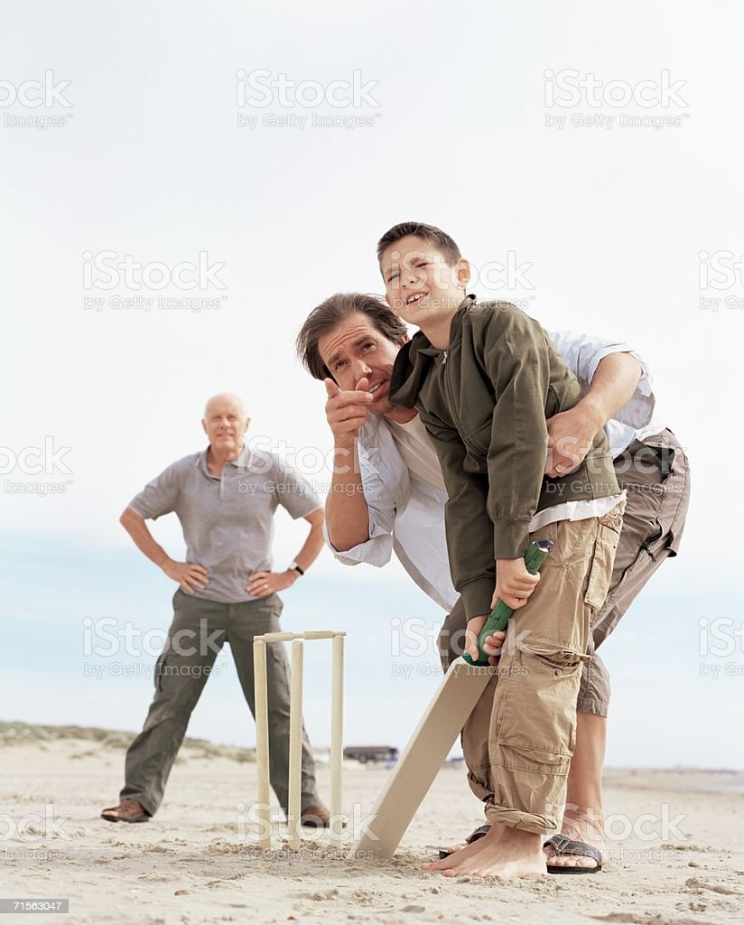 Family playing cricket stock photo