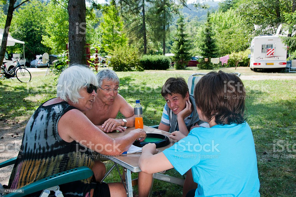 Family playing dice game on campsite 4 royalty-free stock photo