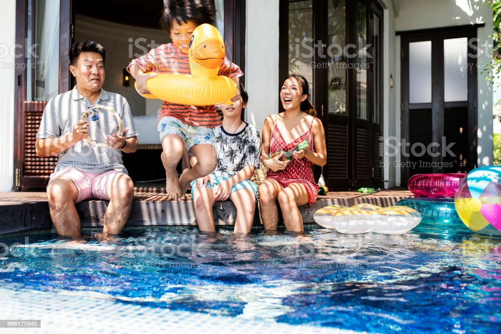 Family playing in a pool stock photo