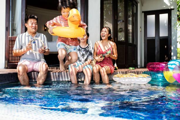 familie in einem pool spielen - asienreise stock-fotos und bilder