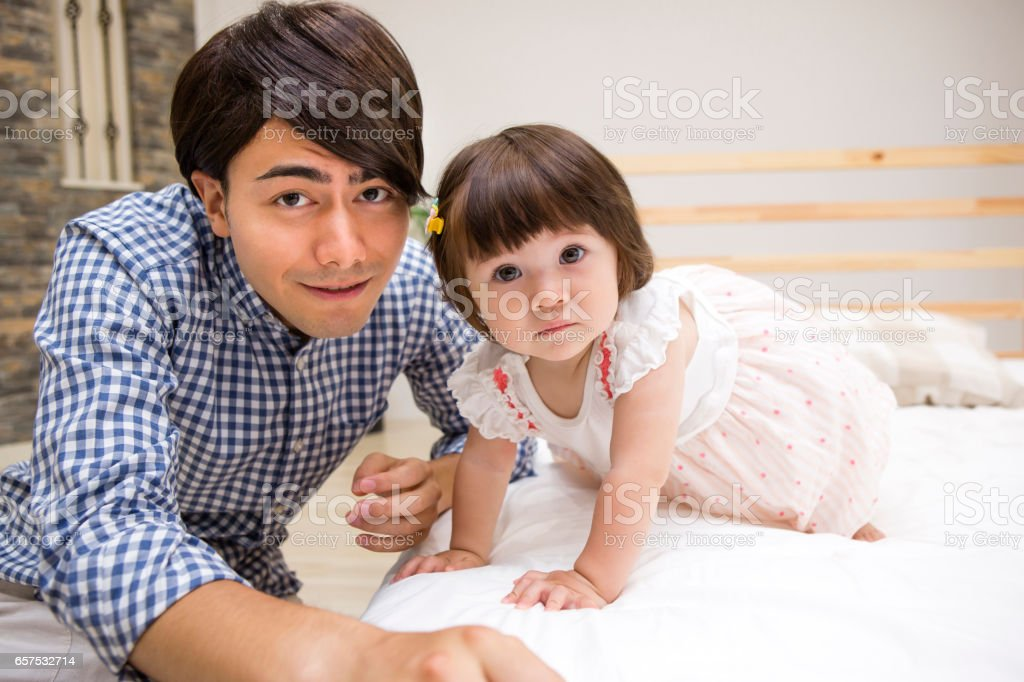 Family playing in bed stock photo
