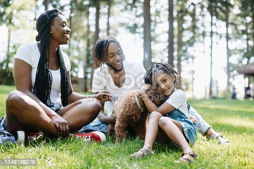 A cute young African American family enjoys relaxation time in a city public park with their pet poodle.  Shot in Tacoma, Washington.