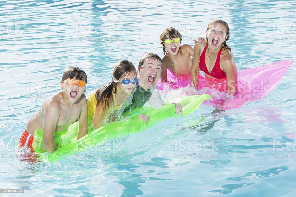 Family playing in swimming pool stock photo