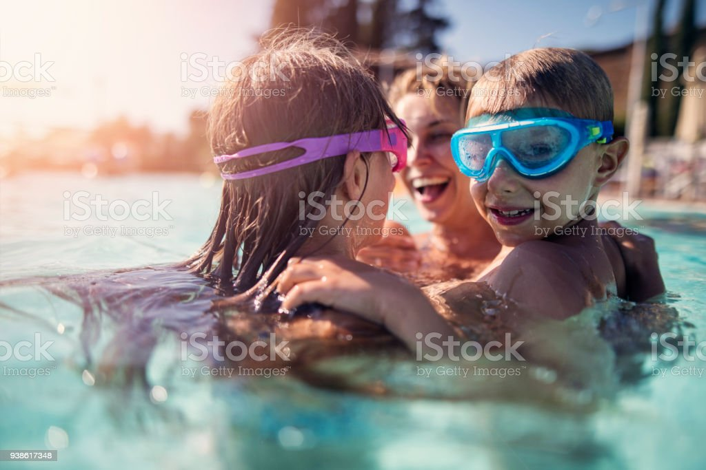 Family playing in swimming pool - foto stock