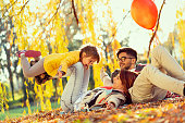 Young family enjoying a beautiful autumn day in nature, having a picnic and spending time together; mother lifting her daughter. Focus on the mother and daughter