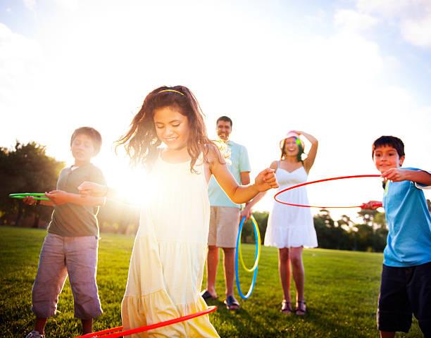 familie spielen im park - hula hoop workout stock-fotos und bilder