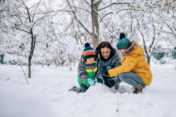 familie im schnee spielen - schneemann bauen stock-fotos und bilder