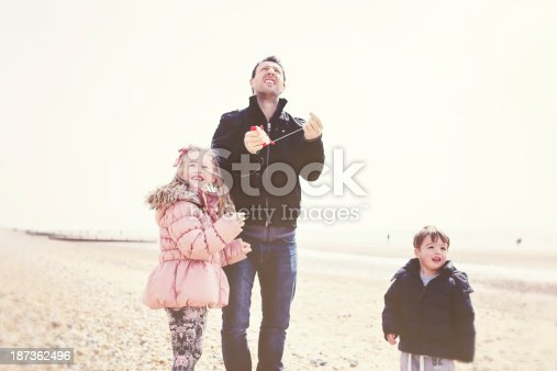 453383283 istock photo Family Playing on Beach with Kite 187362496