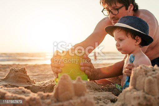 509423868 istock photo Family playing on the beach and building sandcastle on summer holidays 1157552973