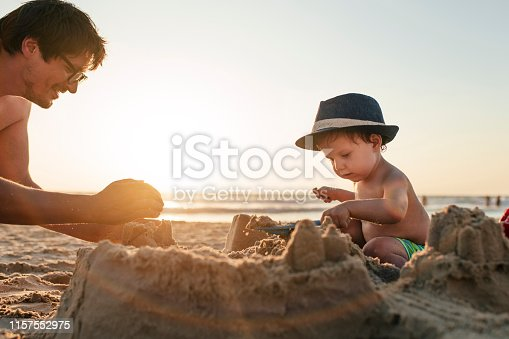 509423868 istock photo Family playing on the beach and building sandcastle on summer holidays 1157552975