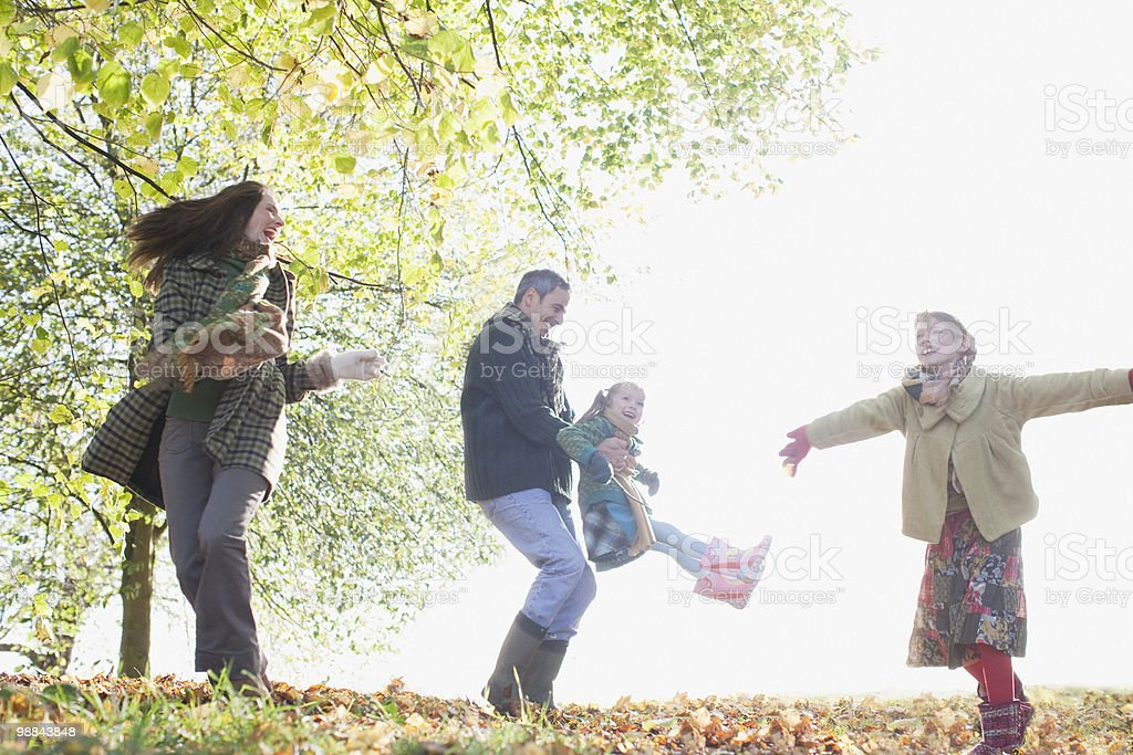 Family playing outdoors in autumn stock photo