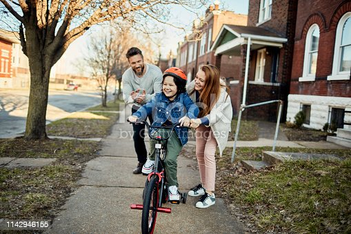 Close up of a father and mother helping their son with learning how to ride a bike