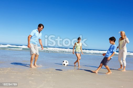 829627936istockphoto Family playing soccer along the beach 183264789