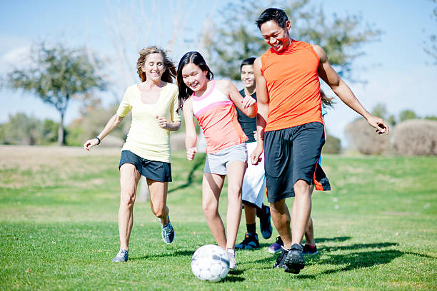 Family Playing Soccer at the Park stock photo