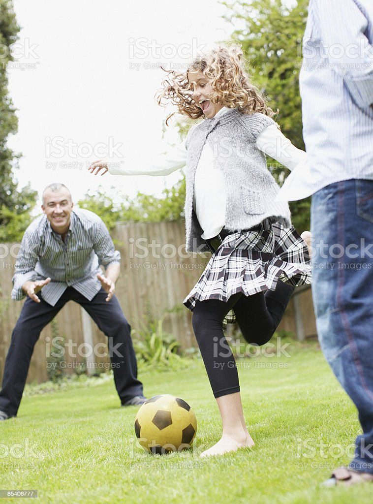 Family playing soccer in backyard royalty-free stock photo