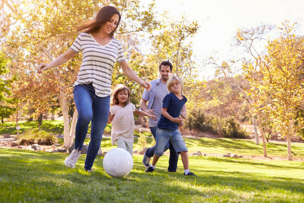 Family Playing Soccer In Park Together stock photo